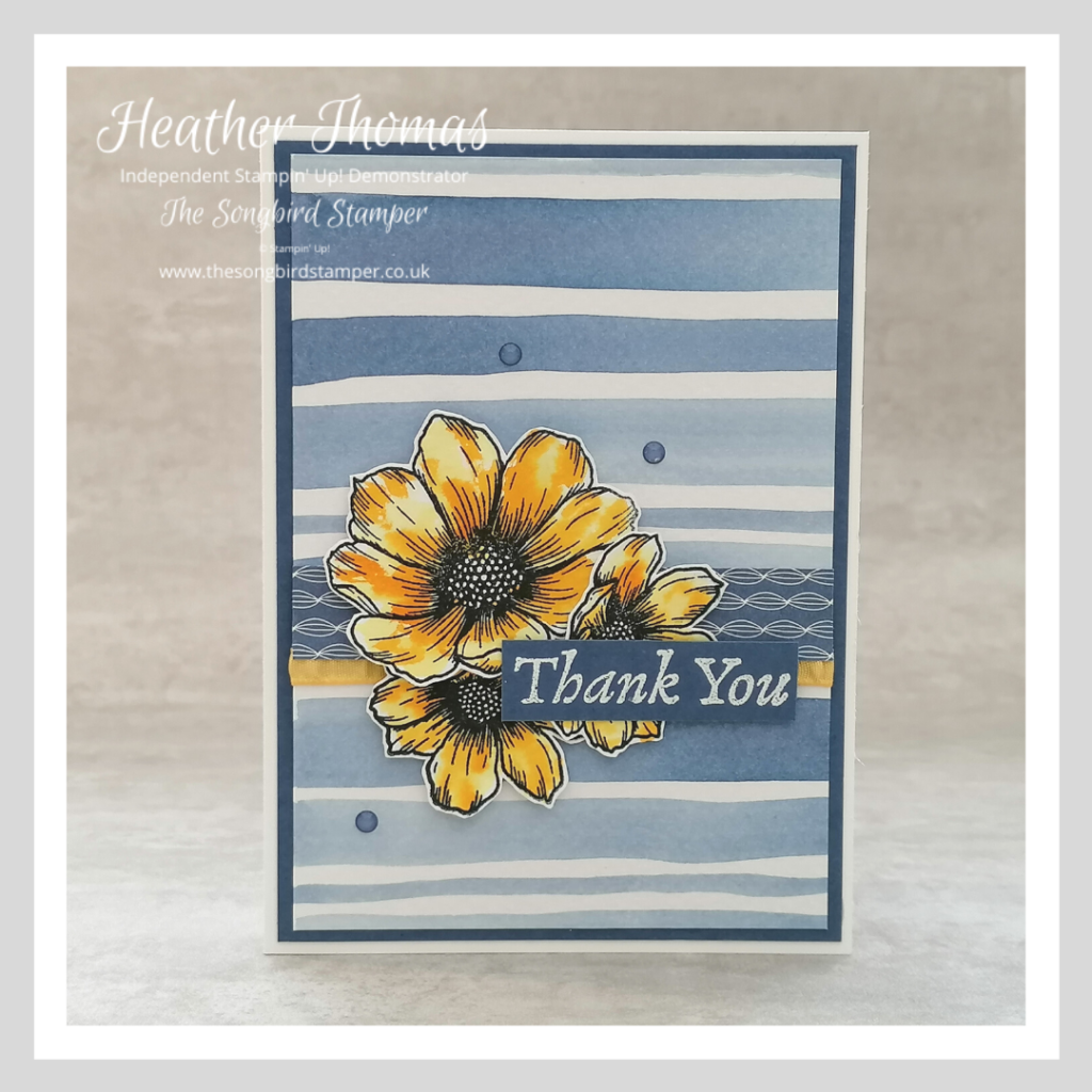 A handmade card with a striped watercolour background