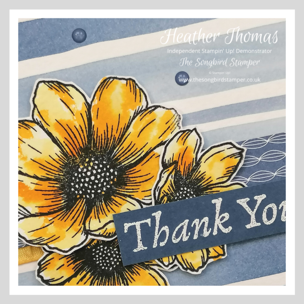 A close up of a handmade thank you card with a striped watercolour background